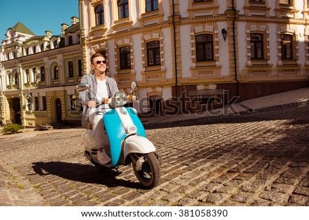 Happy handsome man traveling old city on the scooter - stock photo
