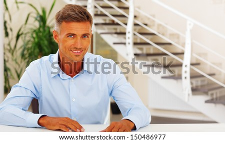 Happy handsome mature man in formal cloths at home