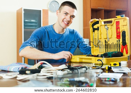 Happy handsome smiling guy sitting at table and showing toolbox - stock photo