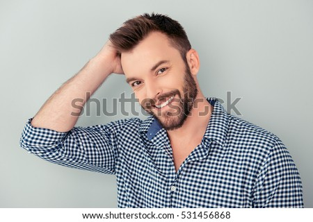 Happy handsome smiling man touching his hair