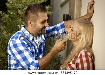 Happy handsome stubbly man, leaning against wall, flirting with young blonde woman outdoor, smiling. - stock photo