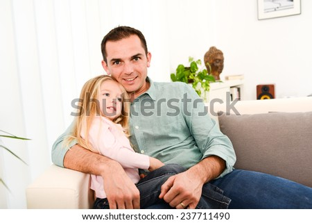 happy handsome young daddy and his young daughter lying down on sofa at home - stock photo