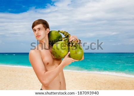 Happy handsome young male beach holding coconuts under the sun on sunny summer day during holidays vacation. Good looking guy in his 20s. - stock photo
