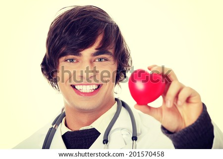 Happy handsome young male doctor holding heart shape toy - stock photo