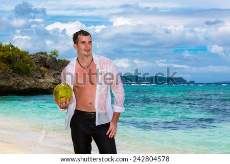 Happy handsome young male wearing in white shirt is standing on the tropical beach is holding coconuts under the sun on sunny summer day during holidays vacation. - stock photo