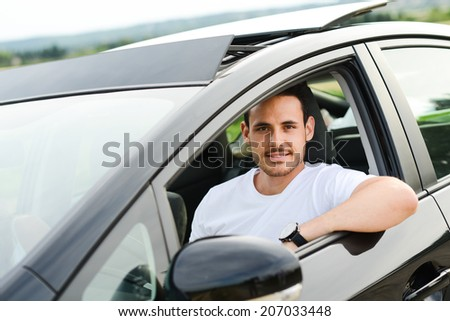 happy handsome young man driving his new car in countryside summer vacation  - stock photo