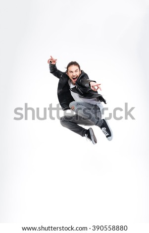 Happy handsome young man showing victory gesture and jumping over white background - stock photo