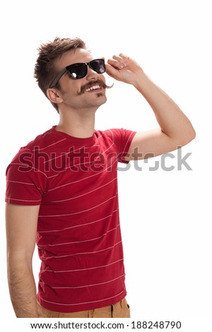 Happy, handsome young man with hipster  looks up, adjusts his sunglasses and smiles, isolated on white background - stock photo