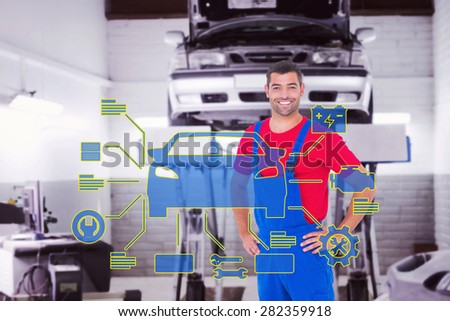 Happy handyman in overalls with hands on hip against auto repair shop - stock photo