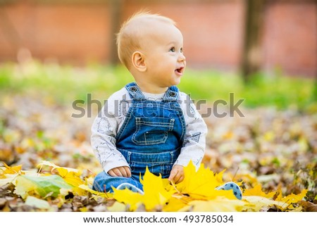 Happy, happy baby sitting in the park with yellow leaves in autumn. In autumn park kid sitting in yellow leaves. Cheerful baby sitting in the park. Warm autumn day in the park.
