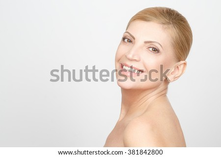Happy health. Horizontal studio portrait of a gorgeous mature woman smiling happily looking over the shoulder copy space on the side