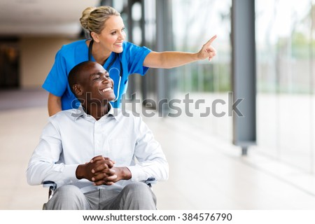 happy healthcare worker taking disabled patient for a walk in hospital - stock photo