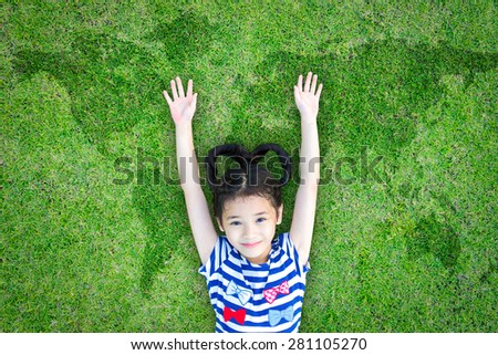 Happy healthy Asian kid with heart-shaped hair raising hands up lying on green grass floor with world map background : Little child has fun activity : Save the planet and healthy environment concept  - stock photo