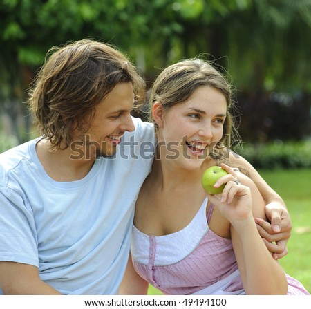 Happy healthy attractive couple with their apple in the park - stock photo