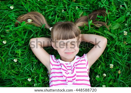 Happy healthy Caucasian kid with heart-shaped hair lying on the grass field background: Peaceful mind girl in clean natural greenery surroundings - stock photo