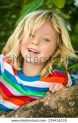 Happy, healthy child climbing a tree at the beach - stock photo