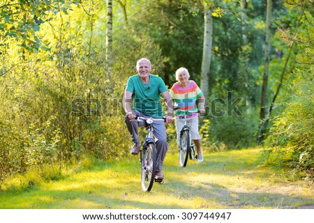 Happy healthy couple biking together in the forest. Seniors enjoying sunny day outdoors. Active retirement concept.