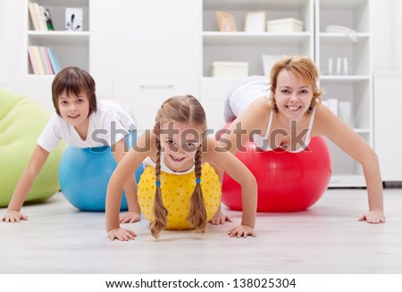 Happy healthy family exercising doing push ups on large balls - at home