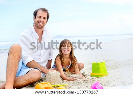 happy healthy family father and daughter building sand castle on the beach smiling and carefree