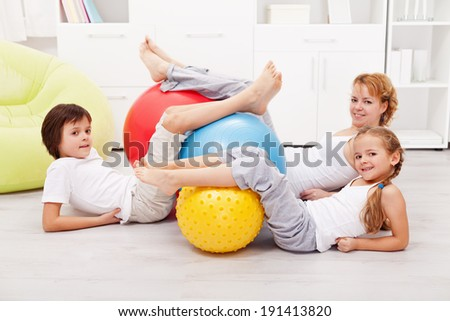 Happy healthy family with large gymnastic rubber balls laying on the floor at home - stock photo