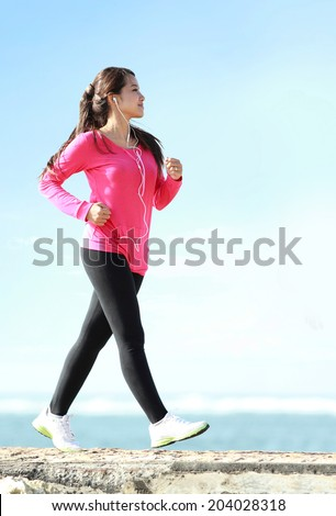 Happy healthy girl doing a brisk walking on the beach - stock photo