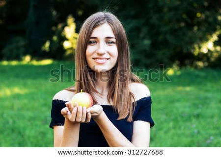 Happy, healthy girl with an apple in his hand resting in a park.