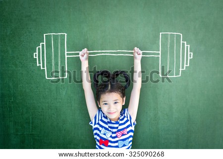 Happy healthy kid doing weight lifting on grunge green chalkboard background: International day of girl child Equality & opportunity awareness on woman human rights Children's day concept Leader idea  - stock photo