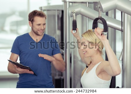 Happy Healthy Pretty Woman Exercising at the Gym with her Young Male Gym Instructor - stock photo