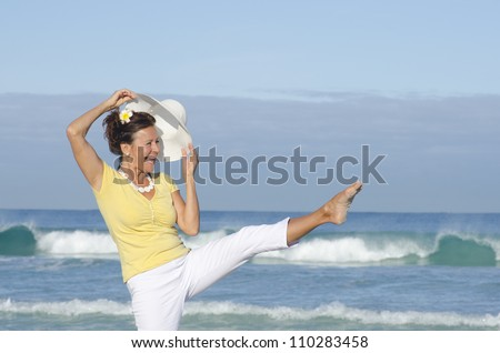 Happy healthy retired woman at the beach, stretching one leg in the air, cheerful laughing, isolated with ocean and sky as background and copy space.