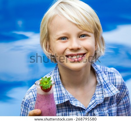 Happy, healthy school child with fresh fruit smoothie by pool - stock photo