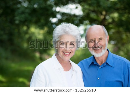Happy healthy senior couple enjoying a day outdoors in the sunshine standing close together smiling at the camera against greenery - stock photo