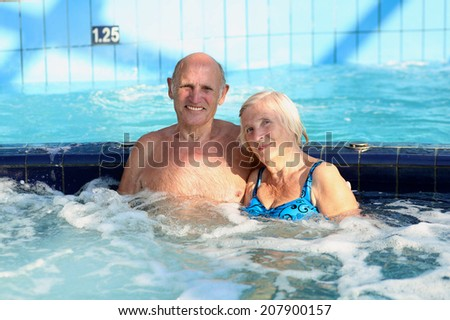 Happy healthy senior couple having fun together in the swimming pool enjoying jacuzzi