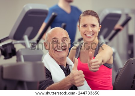 Happy healthy senior man and young woman in a gym giving the camera a thumbs up gesture of success as they look at the camera with beaming smiles