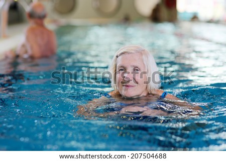 Happy healthy senior woman enjoying active lifestyle swimming in the pool - stock photo