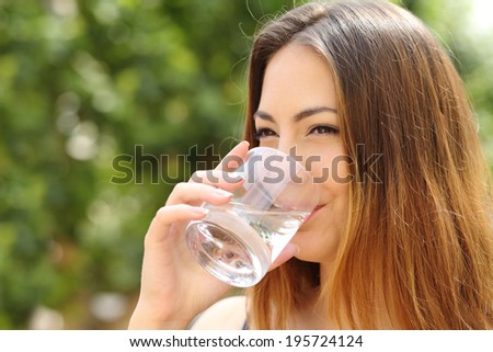 Happy healthy woman drinking fresh water from a glass outdoor with a green background             - stock photo