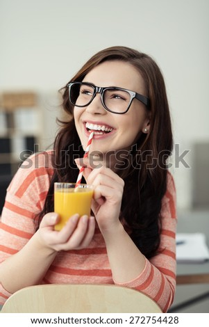 Happy healthy woman drinking orange juice from a glass with a straw beaming as she looks up at something off to the left of the frame - stock photo