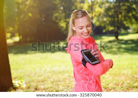 Happy Healthy Young Woman Listening to Music From her Mobile Phone Attached on her Arm Through Earphones at the Park. - stock photo