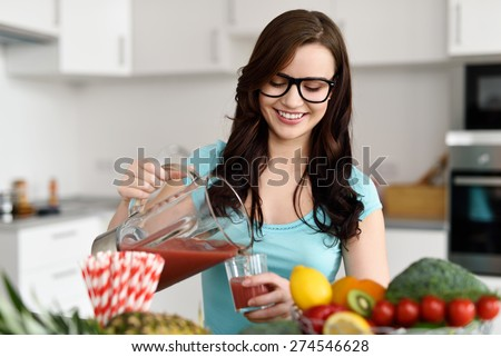 Happy healthy young woman wearing glasses pouring vegetable smoothies freshly made from assorted vegetable ingredients on her kitchen counter - stock photo