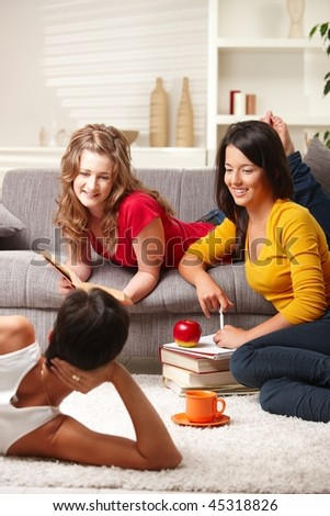 Happy highscool students learning in group at home, smiling.