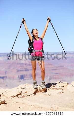 Happy hiker by Grand Canyon cheering and celebrating with arms raised up enjoying the beautiful scenic landscape. Hiking woman wearing backpack and outdoor outfit. Summer in Grand Canyon, Arizona, USA - stock photo