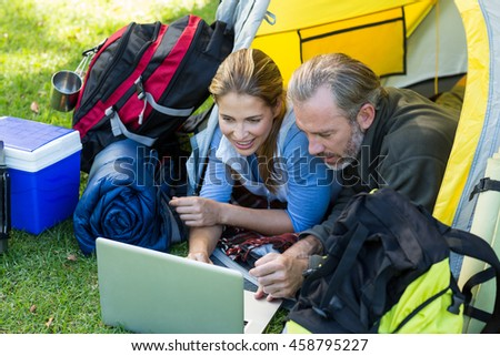 Happy hiker couple using laptop in tent
