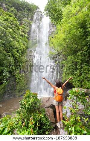 Happy hiker - Hawaii tourists hiking by waterfall. Woman cheering during travel on the road to Hana on Maui, Hawaii. Ecotourism concept image with happy female hiker. - stock photo