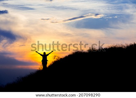 Happy hiker in front of sunset