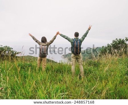 Happy hiker loving couple standing on peak of hill and holding hands each other in summer season - stock photo