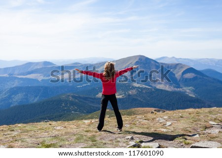 Happy hiker woman standing on a peak over the mountain with raised hands embracing vitality freedom feeling success and looking to a sky. Position back to us - stock photo
