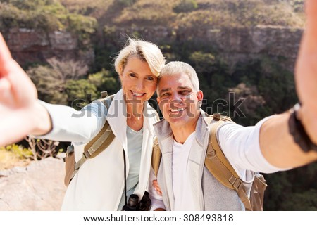 happy hiking couple taking selfie together on top of mountain - stock photo