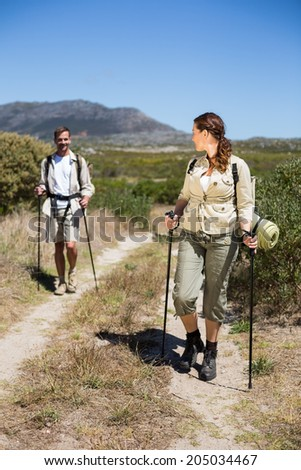 Happy hiking couple walking on country trail on a sunny day
