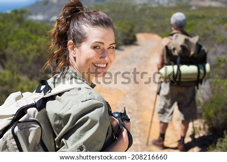 Happy hiking couple walking on mountain trail on a sunny day - stock photo