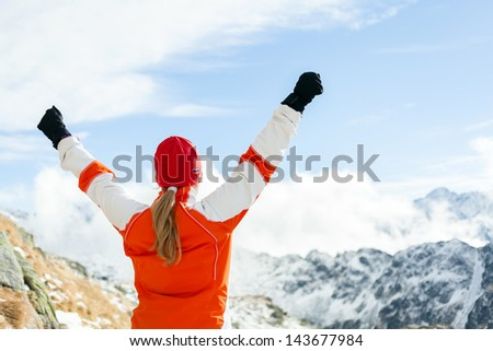 Happy hiking woman and success in mountains, arms outstretched. Motivation and inspiration concept climber fitness and healthy lifestyle outdoors in winter nature on trail mountain ridge - stock photo