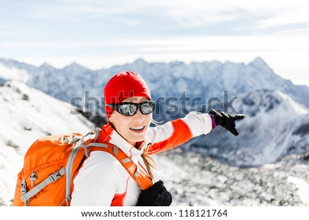 Happy hiking woman and success in mountains. Fitness and healthy lifestyle outdoors in winter nature. Tatra Mountains in Poland on sunny day